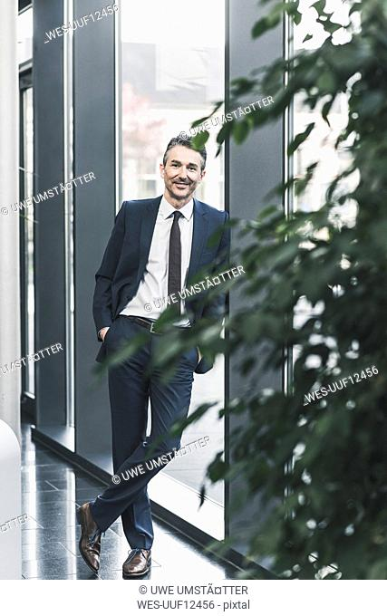 Portrait of smiling businessman standing in office lobby