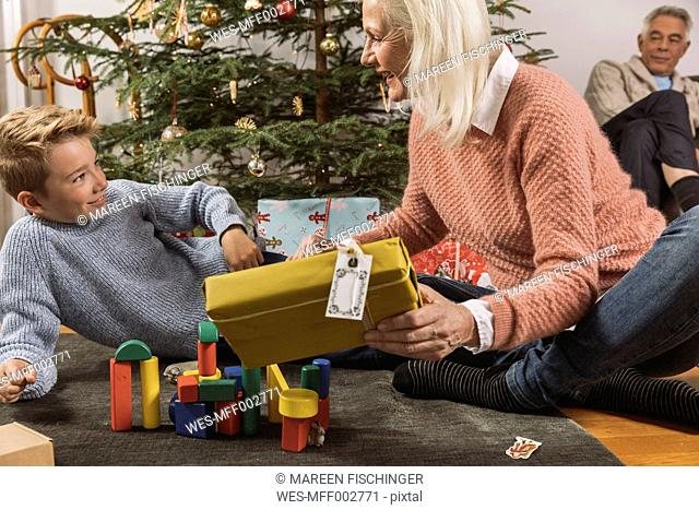 Grandmother giving her grandson a Christmas gift in front of tree