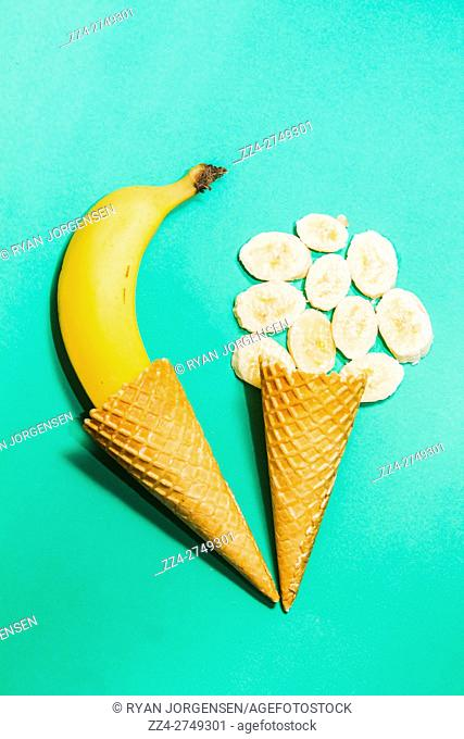 Ice-cream parlour artwork on a creative composition of ice cream waffle cones and ripe bananas on turquoise background