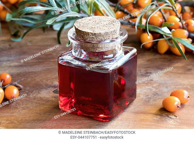 Sea buckthorn oil in a glass bottle on a wooden table, with sea buckthorn berries and leaves in the background