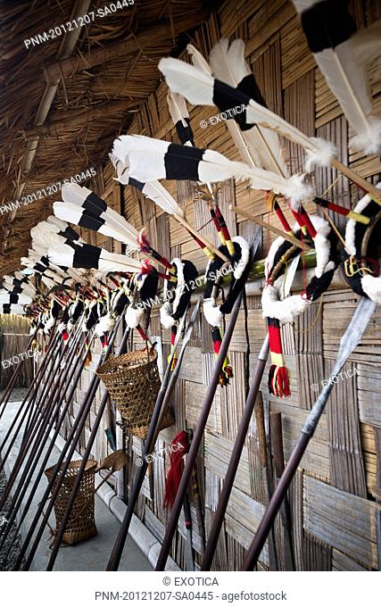 Traditional Naga tribal weapons and headdresses on wall during the annual Hornbill Festival at Kisama, Kohima, Nagaland, India