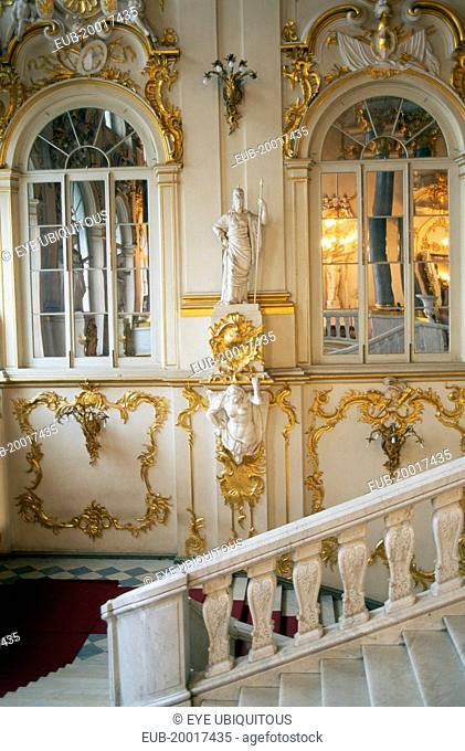 The Winter Palace of the Hermitage Museum. Interior with detail of the Jordan Staircase and walls with gold leaf and plaster motifs reflected in arched mirrors