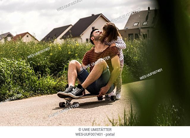 Daughter kissing father on skateboard