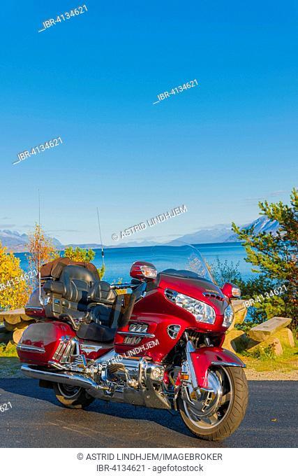 Red motorbike by the ocean, Troms, Norway