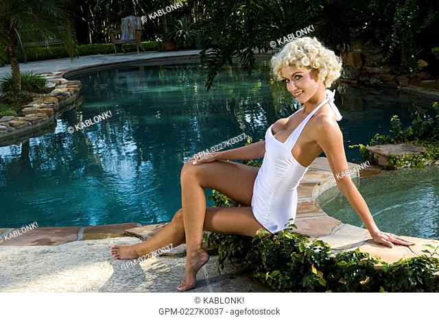 Sexy blonde woman sitting near swimming pool and jacuzzi in vintage bathing suit