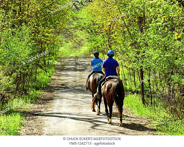 Two female friends riding horses down country backroad