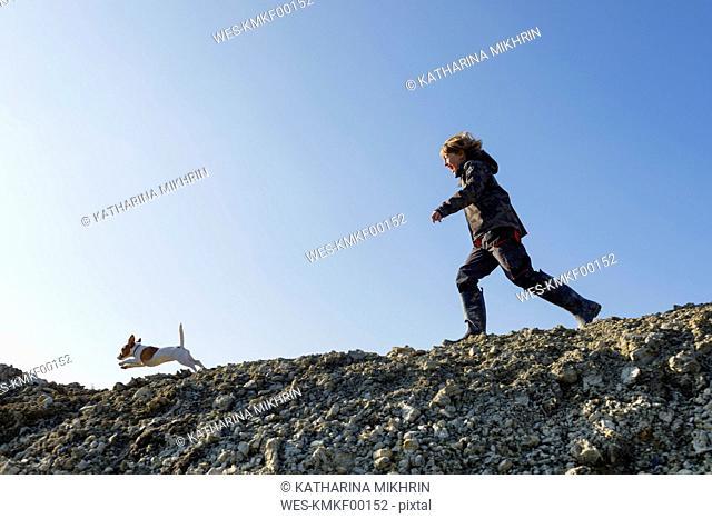 Happy boy running with dog under blue sky