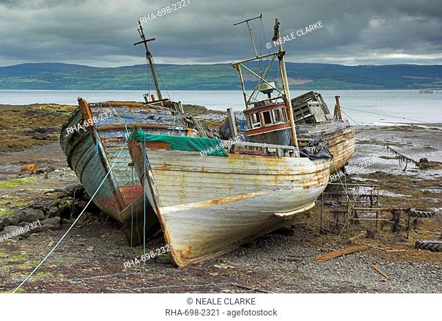 Wrecked fishing boats in gathering storm, Salen, Isle of Mull, Inner Hebrides, Scotland, United Kingdom, Europe