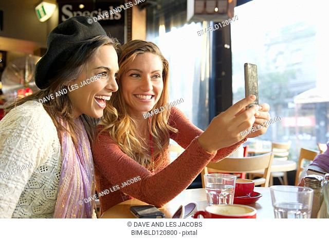 Women taking self-portrait in cafe