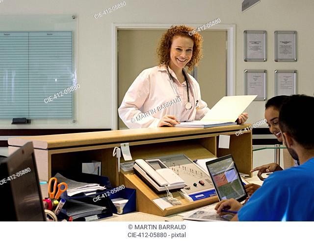 Hospital staff talking at front desk