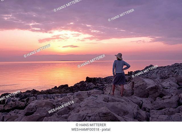 Croatia, Istria, Losinj, woman standing on rocky coast at sunset