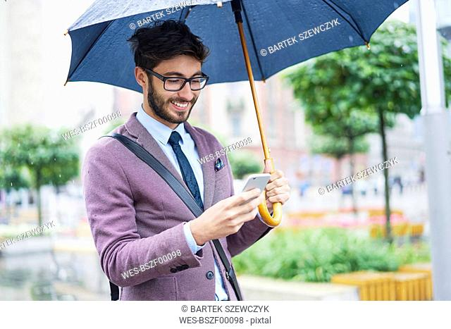 Fashionable businessman with umbrella checking his cell phone in the city