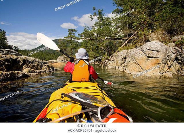 Woman in sea kayak. Kunechin Islets, Kunechin Point, Sechelt Inlet. Gibsons, Sunshine Coast, British Columbia, Canada