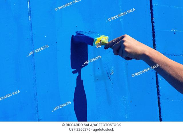 Human Hands Painting Wall with Paintbrush
