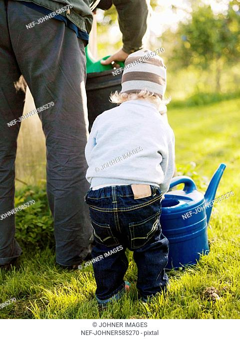 Grandfather and grandchild using a water jug, Sweden