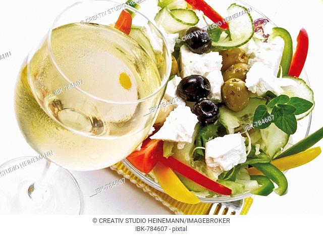 Greek salad with feta cheese, gherkin, tomatoes, and green and black olives and glass of white wine