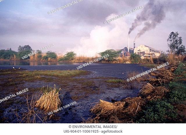 INDIA Uttar Pradesh Sugar Cane. Sugar mill emitting dark clouds of smoke from chimneys beside polluted lake.