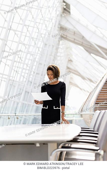 Black businesswoman reading in conference room