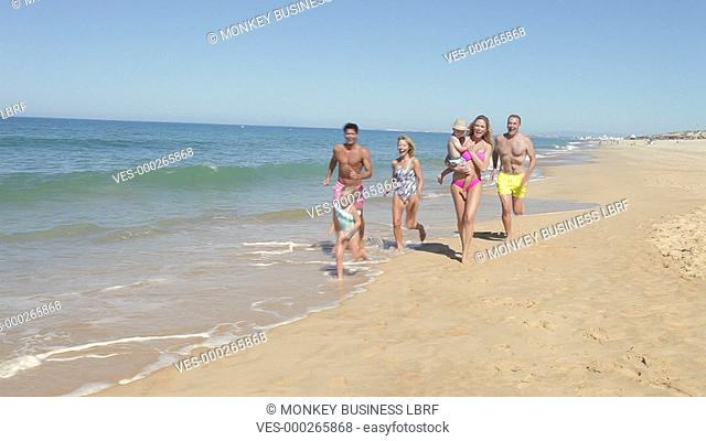 Extended family group running along shoreline towards camera.Shot on Canon 5d Mk2 with a frame rate of 30fps