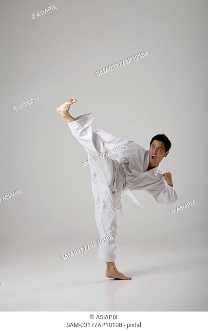 Man kicking high in the air, martial arts