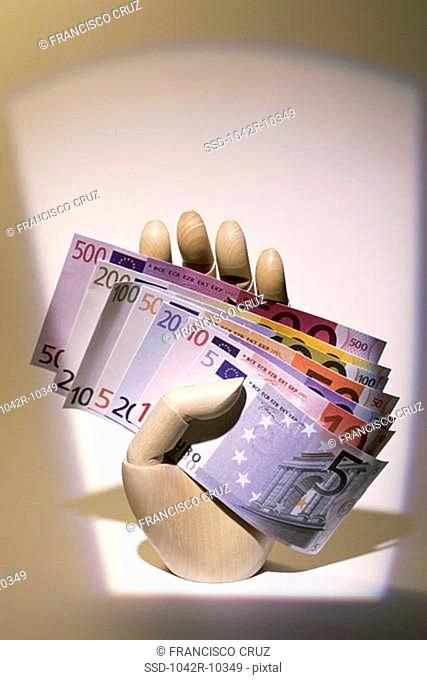 Mannequin's hand holding euro banknotes