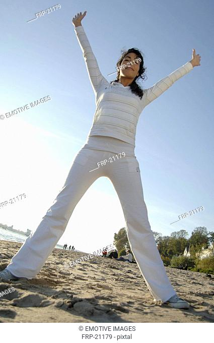 Woman with raised arms on the beach
