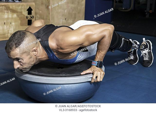 Confident adult sportsman with artificial leg limb doing push-ups on bosu ball