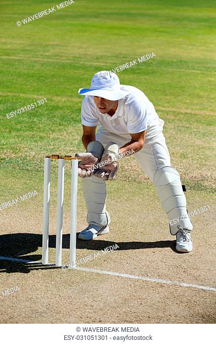 Full length of wicketkeeper standing behind stumps on field