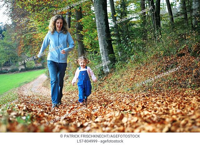 Mother with daughter running on path full of leaves in fall, having fun and laughing, autumn foliage covering path in forest, autumn, fall, Zuerich, Switzerland