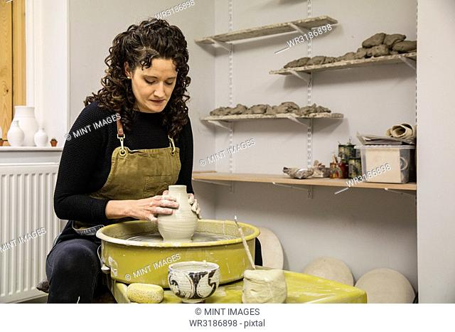 Woman with brown curly hair wearing apron shaping clay vase on pottery wheel