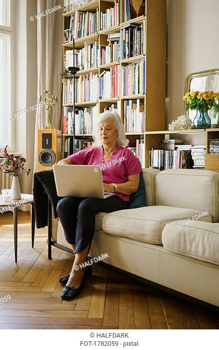 Senior woman using laptop on living room sofa