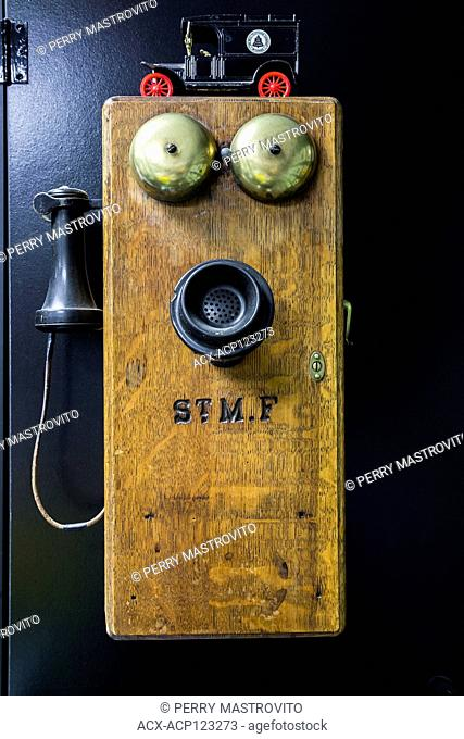 Antique circa 1910 oak wood and black bakelite Plain Front wall mounted telephone with brass ringing bells in the garage inside an old 1927 Canadiana cottage...