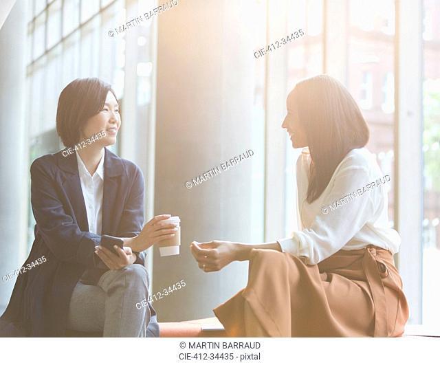 Businesswomen enjoying coffee break talking in sunny lobby