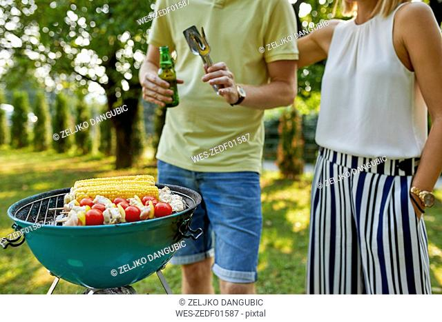Young couple having a barbecue in garden