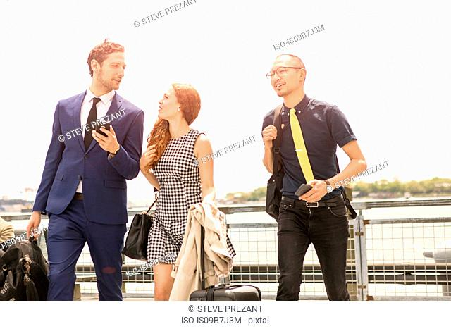 Businessmen and woman walking with luggage on waterfront, New York, USA