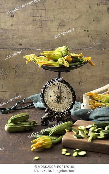 Courgette and courgette flowers with an antique pair of scales