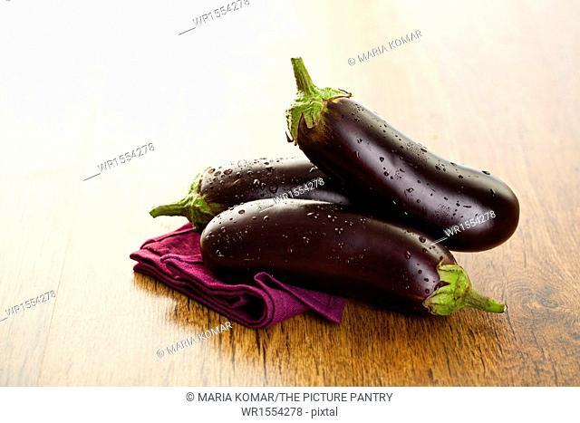Raw aubergines or eggplants on wooden backround