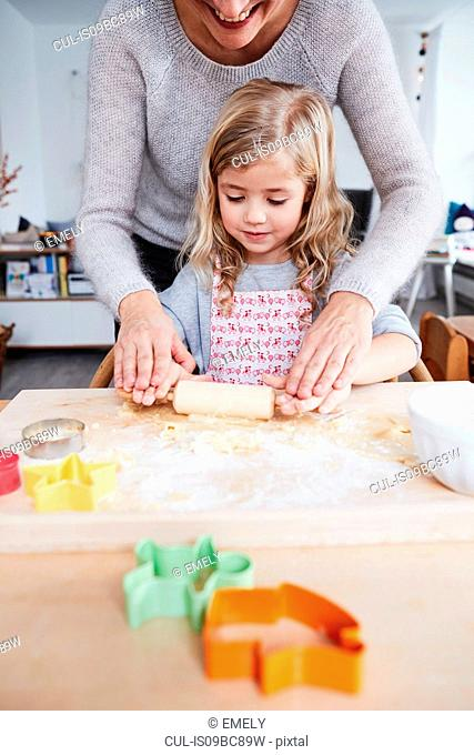 Mother helping daughter roll out cookie dough on kitchen table, mid section