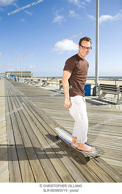 Man skateboarding on boardwalk