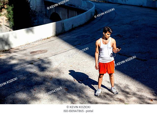 Jogger selecting music on smartphone, Arroyo Seco Park, Pasadena, California, USA