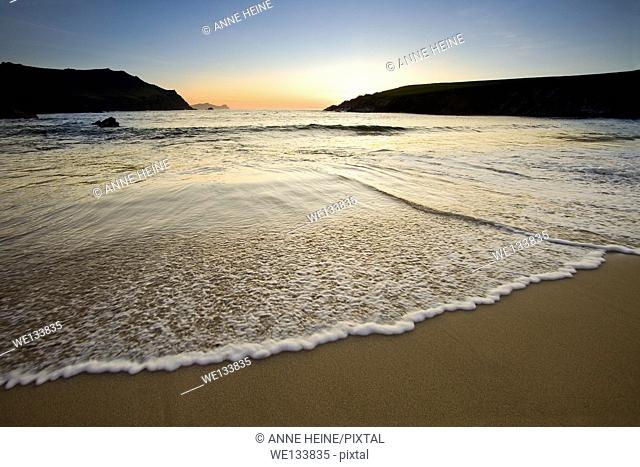 wave speeding into sandy beach at twilight,dingle,ireland