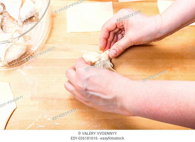 woman prepares dumplings from rolled dough on table