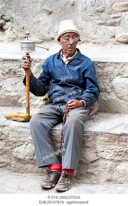 Elderly man praying with prayer wheel in the square near the kings palace