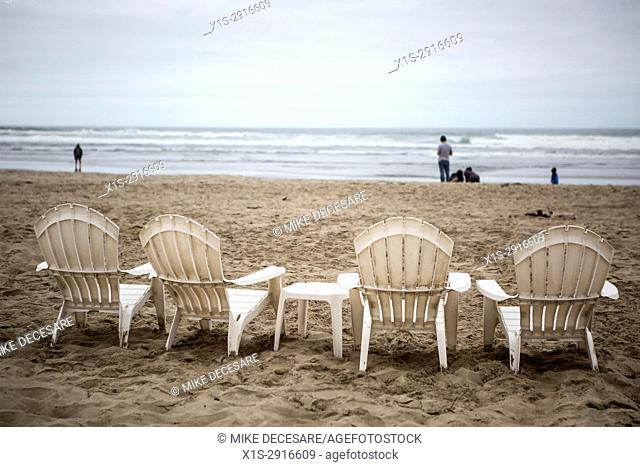 Beach chairs in a row on a sandy beach to watch the Pacific Ocean