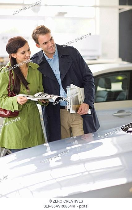 Couple admiring car in showroom