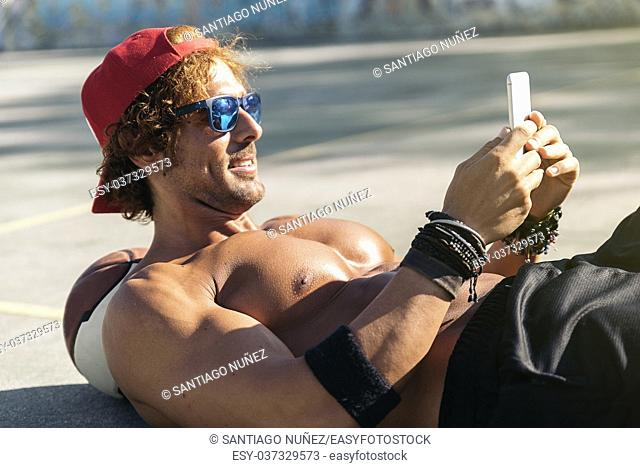 Handsome Man Using a Mobile Phone in a Street Basketball Court