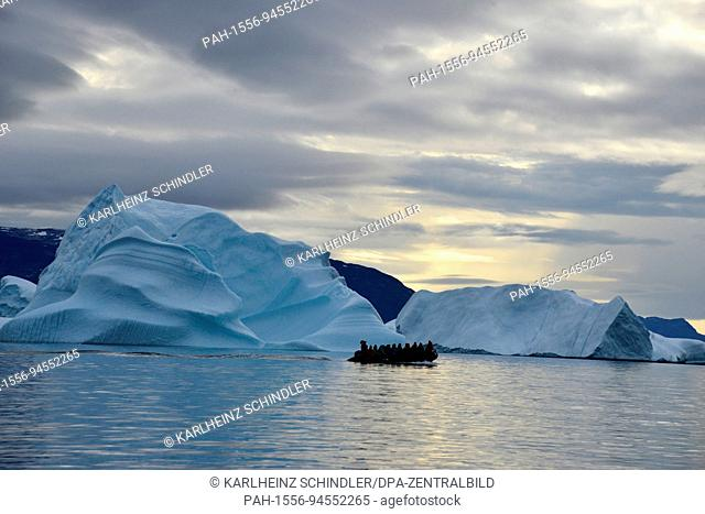 A dinghy with tourists next to the icebergs between the Nuusuaq peninsula and Disko Island near the settlement of Saqqaq on the west coast of Greenland