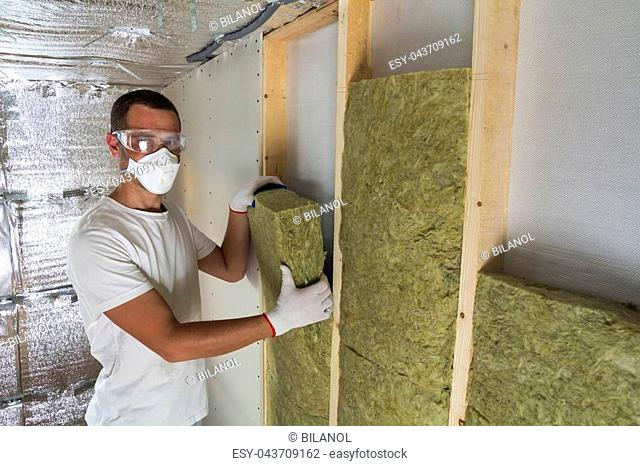 Young worker in respirator insulating rock wool insulation staff in wooden frame for future house walls for cold barrier