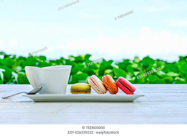 macaroon multicolored with a cup of coffee on white table with sea and blue sky background