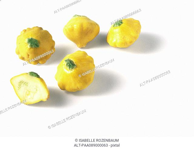 Yellow pattypan squashes, one cut in half